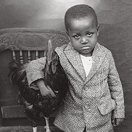 little boy with his pet chicken