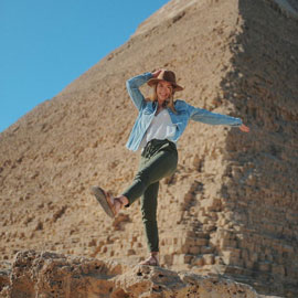 Genevieve Sanders stands in front of an Egyptian pyramid
