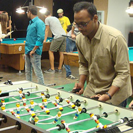 Students hanging out in the Golden Spur Game room. In the front of the photo several students are playing foosball and in the background there are students playing pool.