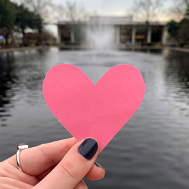 A hand holding pink heart paper cutout in front of the Thomas Cooper Library and fountain
