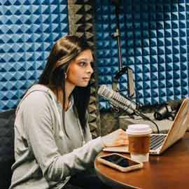 Prer Shidhaye sits at a laptop and microphone to record her podcast