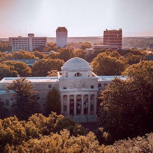 A drone photo that is a bird's eye view of campus, specifically focused on the McKissick Museum surrounded by vibrant fall orange and yellow foliage
