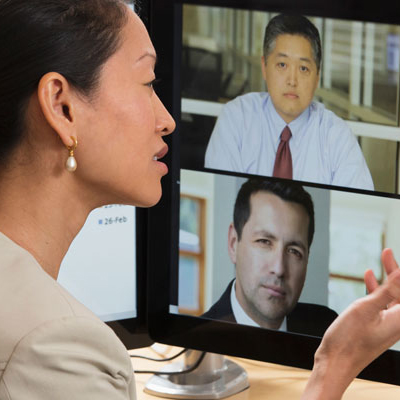 woman in front of computer screen videoconferencing with co-workers