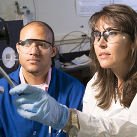 Technicians in a lab wearing gloves and safety goggles.