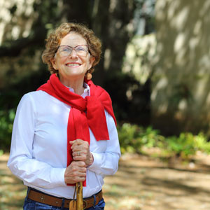 woman wearing glasses in white shirt with red sweater tied around shoulders and holding a walking stick with foliage in the background
