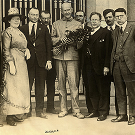 Eugene Debs, at center with flowers, who was serving a prison sentence for violating the Espionage Act, on the day he was notified of his nomination for the presidency on the socialist ticket by a delegation of leading socialist