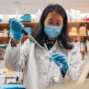 person with dark hair in lab wearing lab coat, blue mask and blue gloves