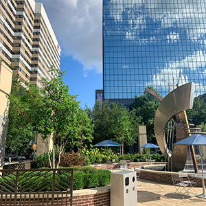 At Boyd Plaza in front of the Columbia Museum of Art, green trees and shrubs surround a metal sculpture. Office buildings and a blue sky are in the background.