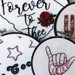 "Allison Lambert's embroidered artworks include the ""Spurs Up"" hand sign and an outline of the state of South Carolina with ""Forever to Thee"" embroidered inside"