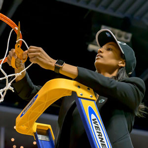 cynthia jordan wearing a ball cap stands on a ladder to cut the net after a big win