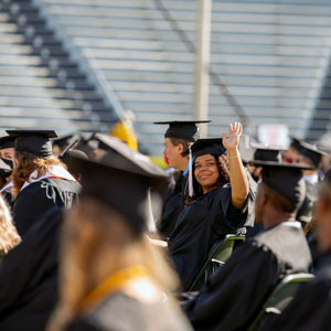 Among a sea of graduates in black caps and gowns, a student turns and waves.