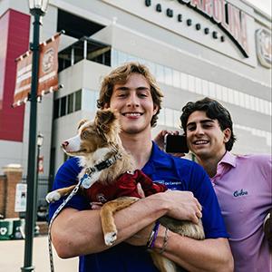 Evan Walker, left, holds his dog in front of Williams-Brice Stadium.
