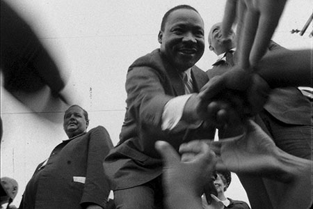 Martin Luther King Jr. clasps hands with attendees