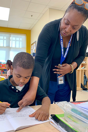 Collins instructs student in first grade