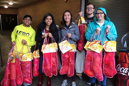 Students from the Carolina Service Council holding stockings full of donation items.