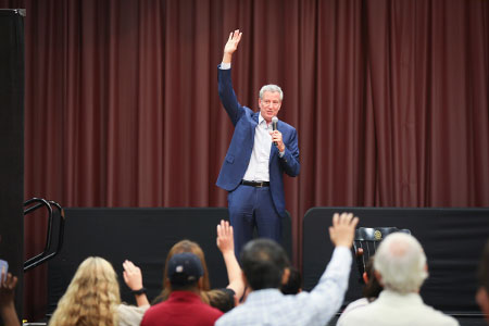 Presidential candidate Bill DeBlasio, holding a microphone and gesticulating with his right hand, speaks to a gathering of people in the Russell House Theater.