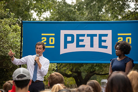 Mayor Pete Buttigieg gestures to a sizeable crowd as Lyric Swinton stands to the right. Both are standing in front of a blue Pete 2020 sign on the Russell House Patio.