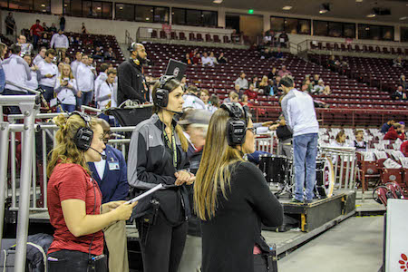 Students working at a basketball game at CLA