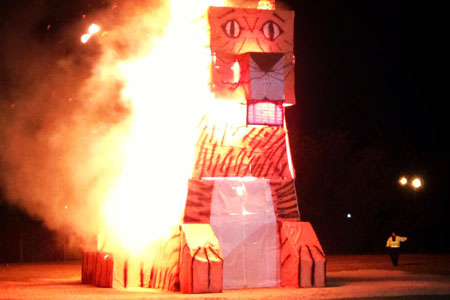 A recent image of the Tiger Burn. This is a large tiger made from a wood frame and paper. It is set ablaze.