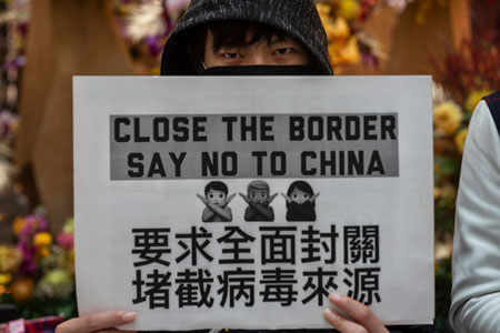 protester holds sign calling for closing the border