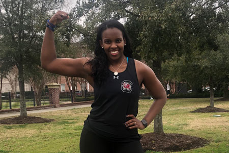Group X fitness instructor, Elizabeth Thompson standing outside flexing her bicep