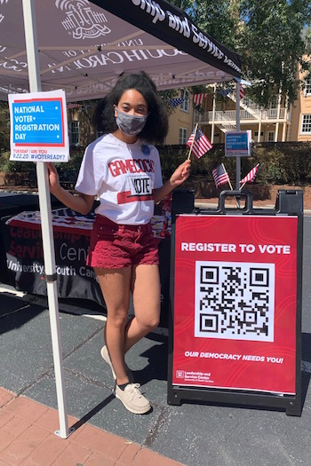"Antonia Adams, a member of CLEAT, on Greene Street for voter registration day. Her shirt says ""Gamecocks Vote"" and she is standing by a sign that says ""register to vote"" and has a QR code on it."