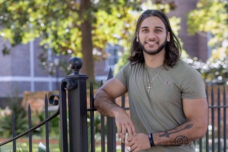 Professional photo of first-generation education student, Dawson Tate, outside on camus, leaning on a black iron fence/gate.