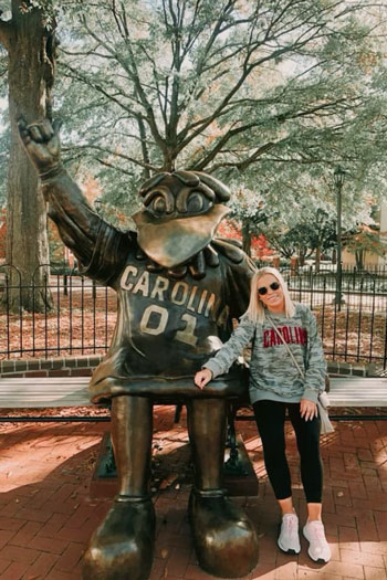 Student Body President Issy Rushton sitting next to UofSC's life-size Cocky statue