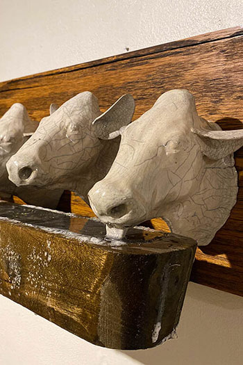 Sculptures of four cow heads are mounted on a wooden panel in front of a drinking trough.