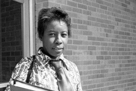 Edna Smith primus in a collar shirt and tie stands outside a building in a 1970s era photo