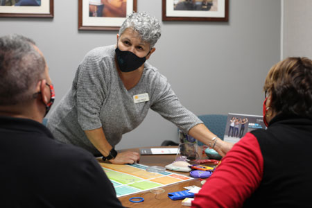 Woman with gray hair, gray shirt and black mask stands in front of a table with health items. Man and woman at table with backs to viewer.
