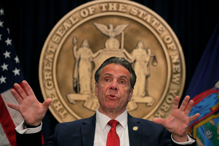 New York Gov. Andrew Cuomo in front of a seal of the state of New York