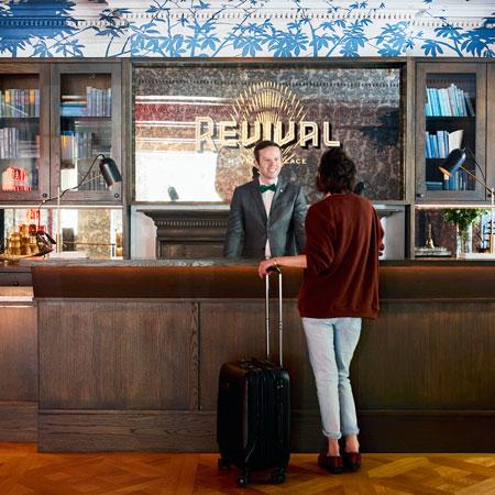 woman talks to hotel clerk in lobby